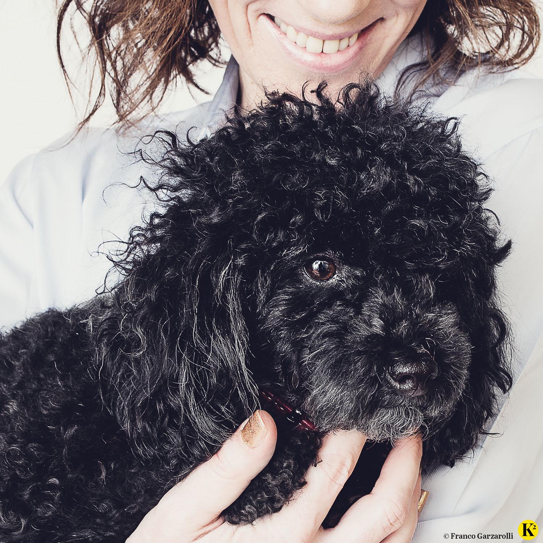 Lächelnde Frau mit schwarzem Toy-Pudel am Arm.