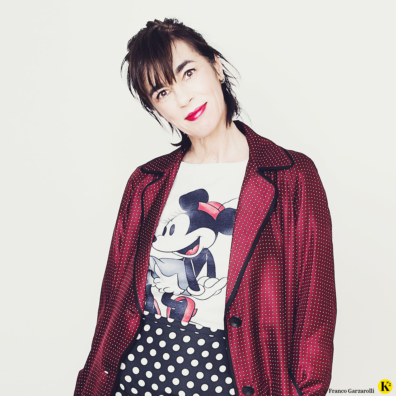 Karin trägt einen schwarzen Bleistiftrock mit weißen Punkten plus Minnie-Maus-Sweater und Seidenmantel in Bordeaux.