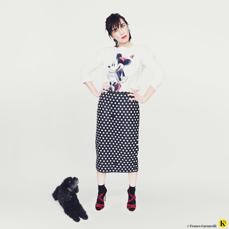 Karin trägt einen schwarzen Bleistiftrock mit weißen Punkten plus Minnie-Maus-Sweater.
