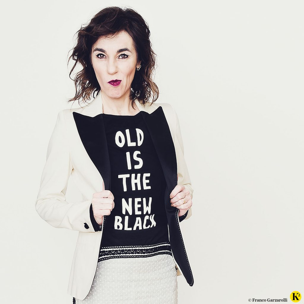 """Karin trägt ein schwarzes T-Shirt mit der Aufschrift """"Old is the new black"""" und schaut lustig in die Kamera. Weiters trägt sie einen cremefarbigen Rock und ein cremefarbiges Blouson."""