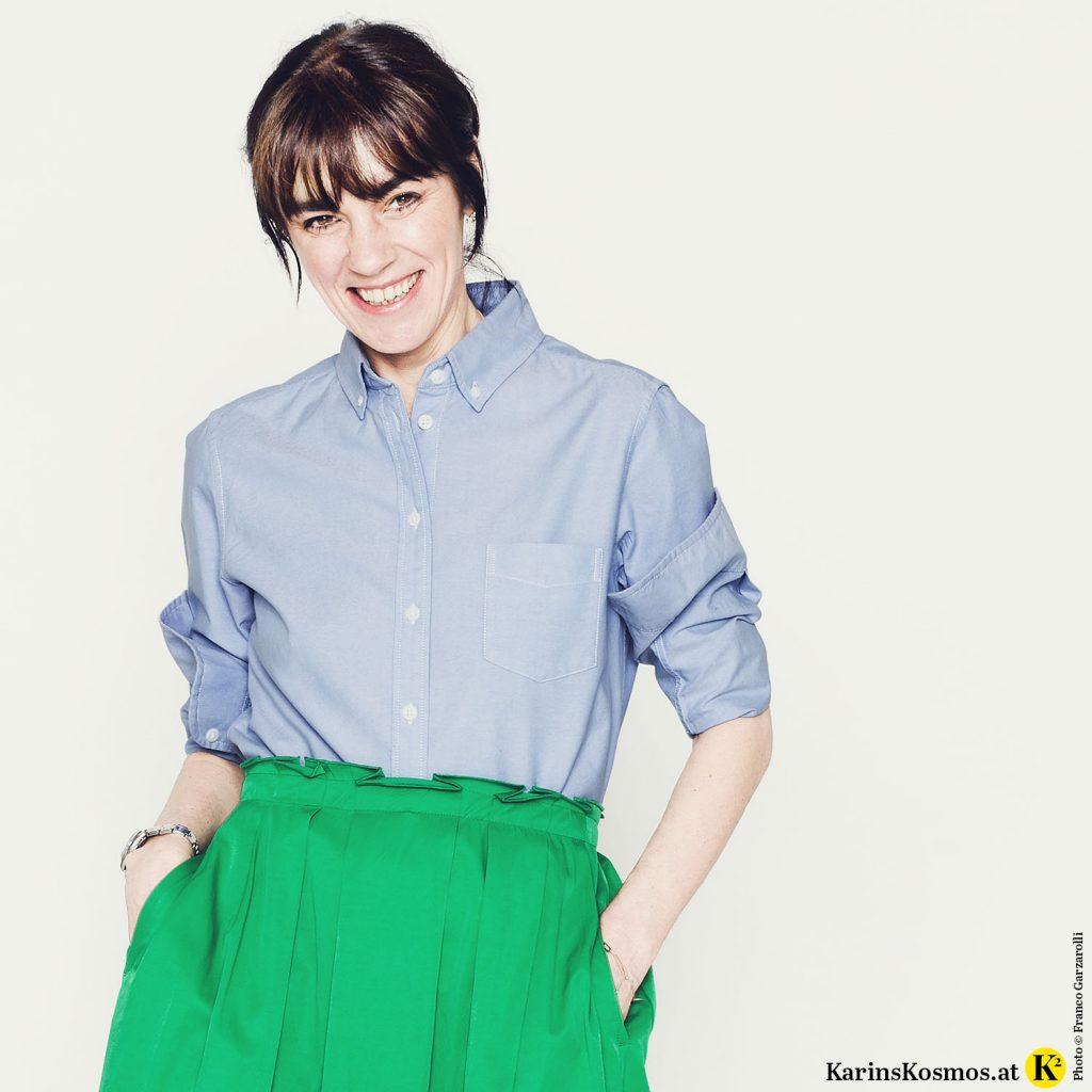 Lächelnde Frau mit blauem Hemd und grünem Rock.