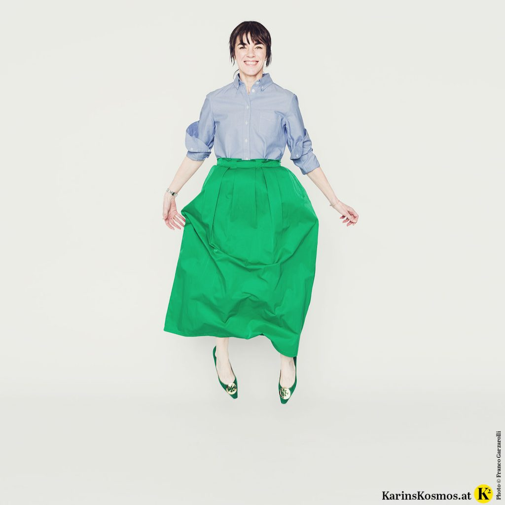 Frau springt in hellblauer Button Down-Bluse mit grünem, langem Rock und grünen Ballerinas.