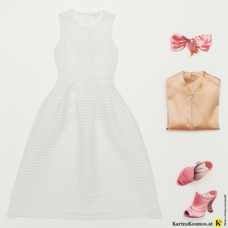 Produktfotografie mit weißem Kleid, Haarband mit Feder, Bomberjacke und Mules aus Satin.