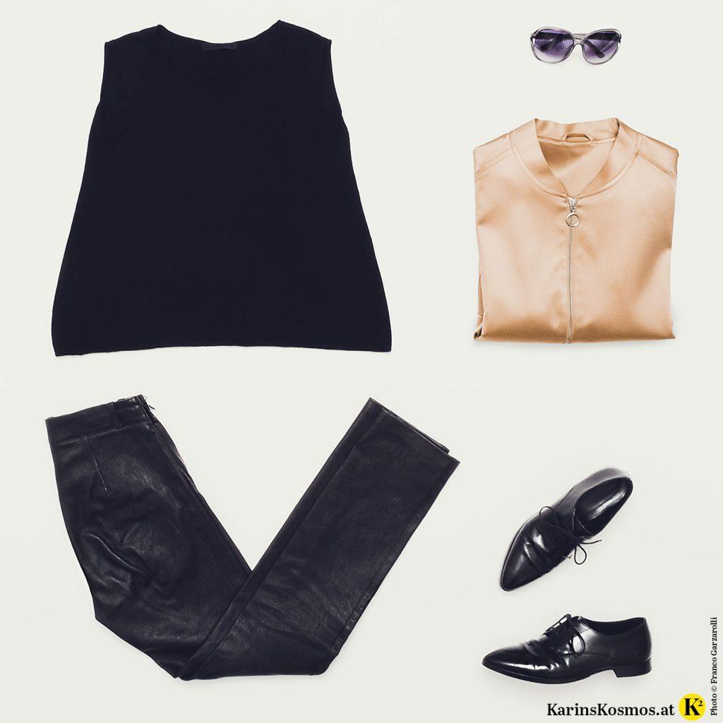 Produktfoto mit ärmellosem Kaschmir-Top, Lederhose, Sonnenbrillen, Bomberjacke und Schnürschuhen.
