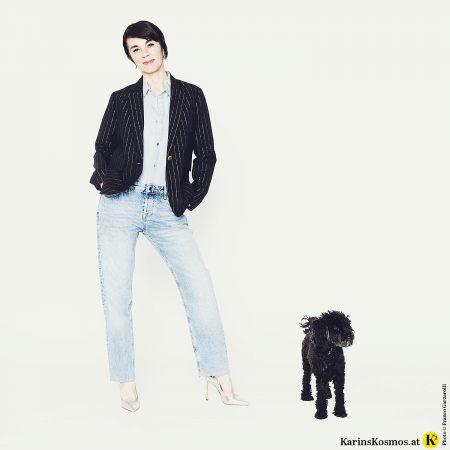 Frau trägt Jeanshemd und Jeans zu schwarzem Blazer und goldenen Schuhen. Daneben ein schwarzer Pudel.