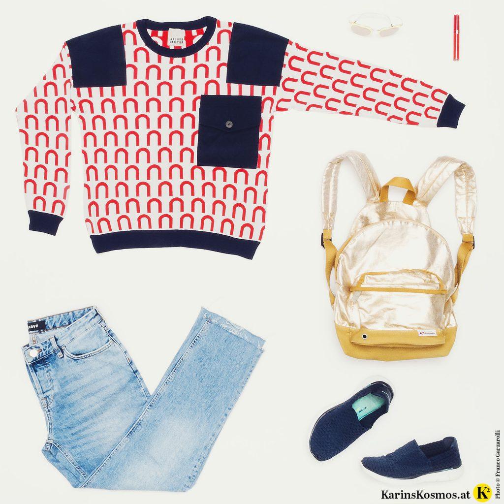 Produktfoto von einem rotgemusterten Pullover, einer Jeans, einem goldenen Rucksack, einer Sonnenbrille, einem roten Lippenstift und blauen Schuhen.