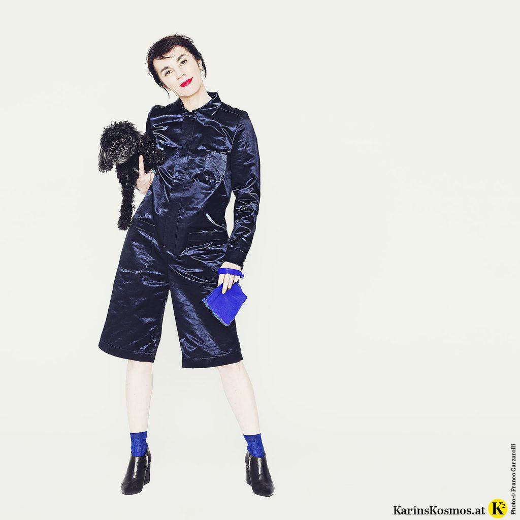 Frau mit Toypudel Trudy am Arm in mitternachtsblauem Overall mit Clutch und Ankle-Boots.