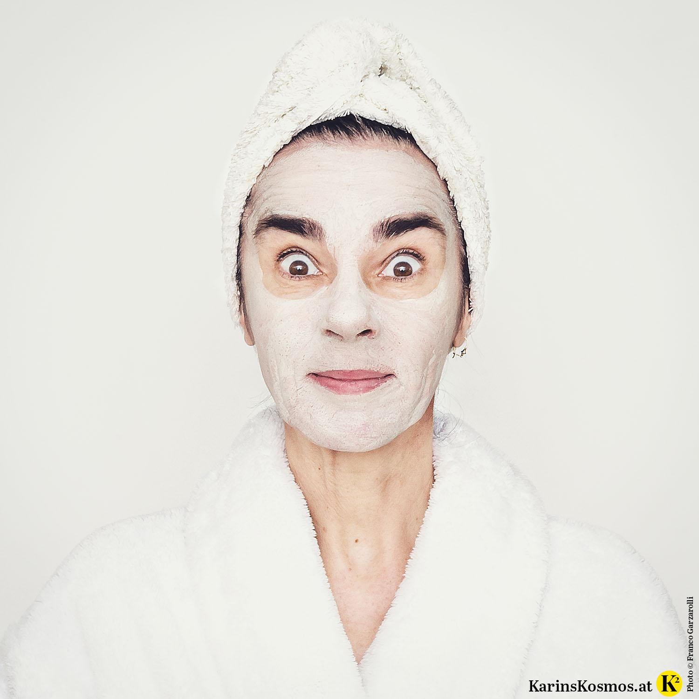 Frau mit Handtuch am Kopf und Bademantel mit Maske im Gesicht.