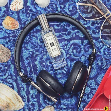 Stilllife mit Parfumflakon von Jo Malone, Nutmeg & Ginger, Kopfhörer, Muscheln, Sonnenbrillen auf blauem Tuch.
