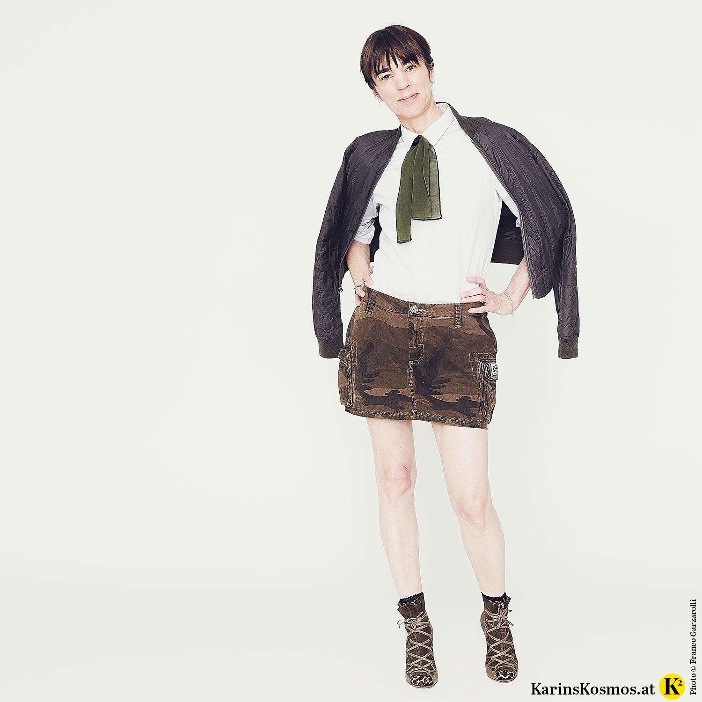 Frau in Minirock mit High-Heels, weißer Bluse und Bomberjacke.