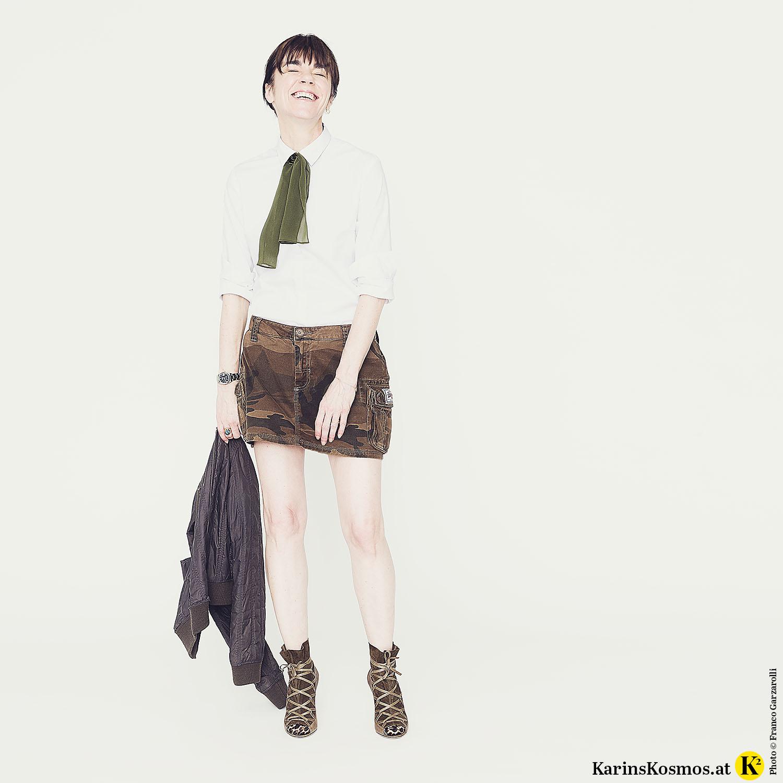 Frau in Minirock mit weißer Bluse, Seidenschal, Bomberjacke und High-Heels.
