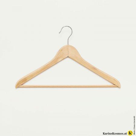 Foto von einem Holzkleiderbügel als Symbol für einen Kleiderschrank.