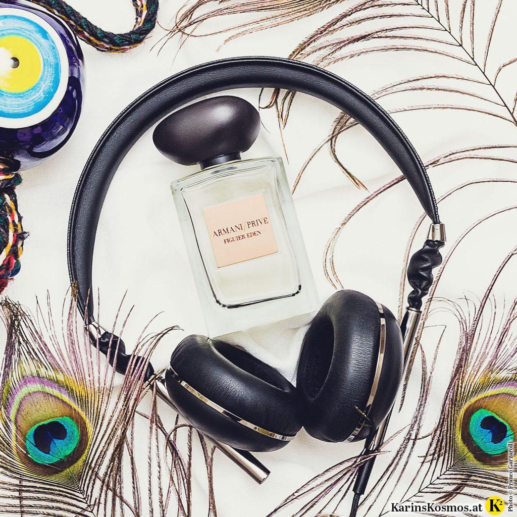 Foto mit einem Parfumflakon, Kopfhörer, Pfauenfedern und einem griechischen Auge.