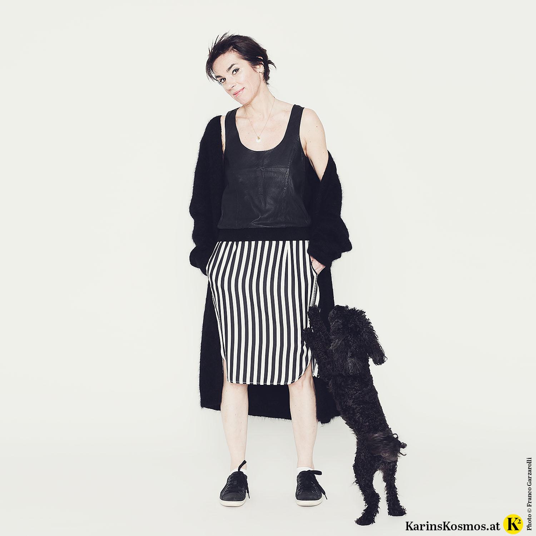 Frau mit Rock mit schwarz/weißen Streifen, schwarzem Top und Strickmantel zu schwarzen Turnschuhen. Dazu ein schwarzer Toypudel.