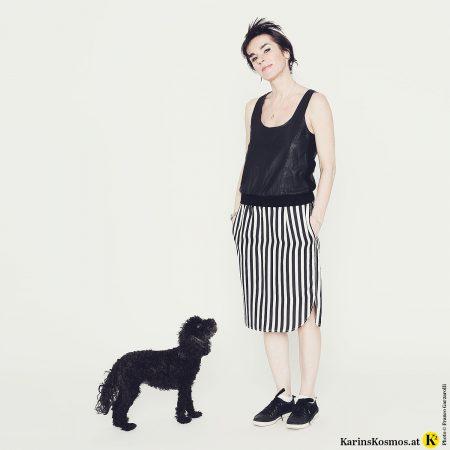 Frau in schwarzem Top, Seidenrock mit schwarz/weißen Streifen und schwarzen Sneakers. Vor ihr steht ein schwarzer Toypudel.