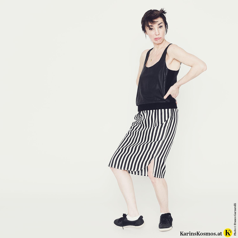 Frau in Seidenrock mit Streifen und schwarzem Top macht eine lustige Grimasse.