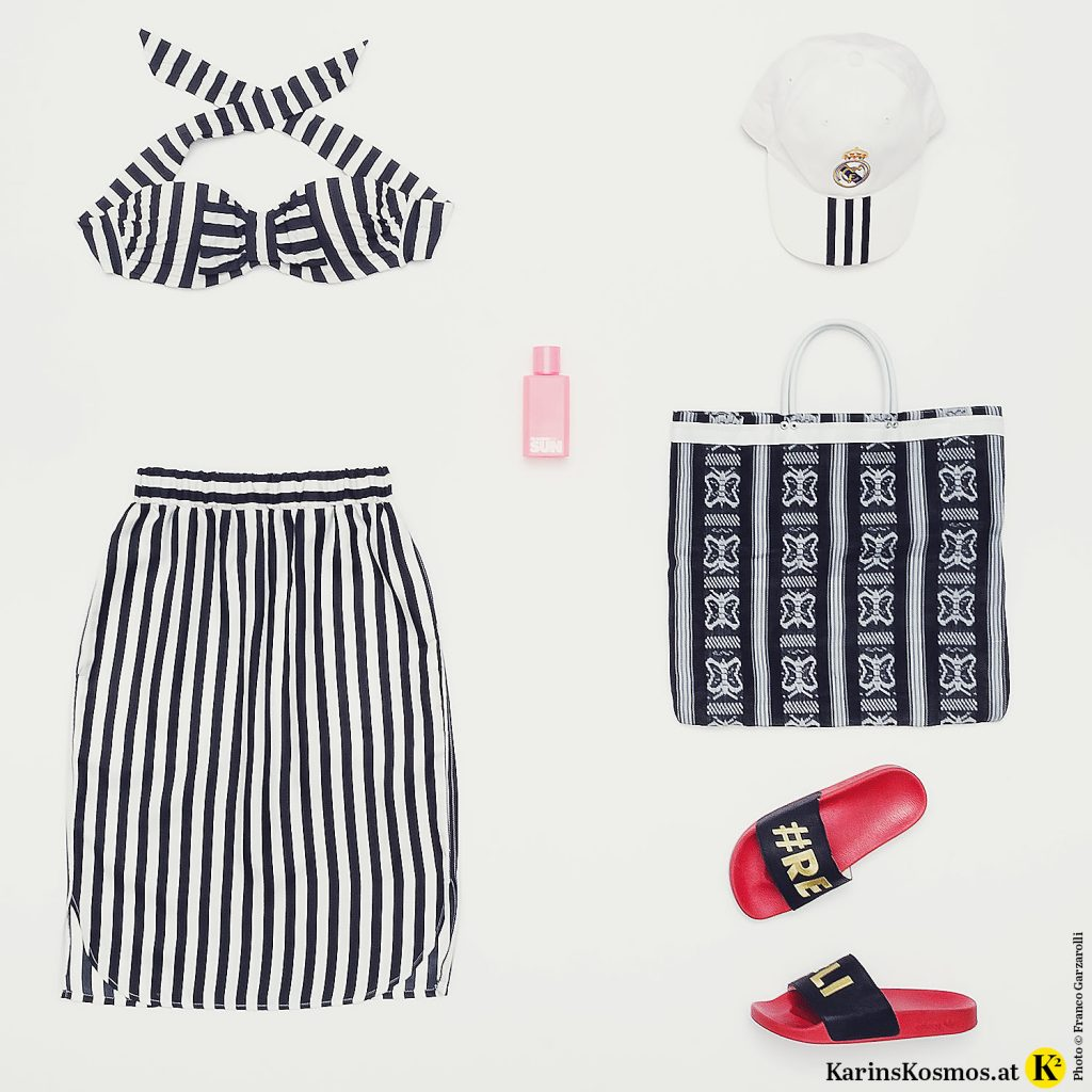 Produktfoto mit Bikinioberteil und Seidenrock mit schwarz/weißen Streifen, Jil Sander Sun Eau de Toilette, Real Madrid-Kappe, Strandtasche und Badeschlapfen von Adidas.