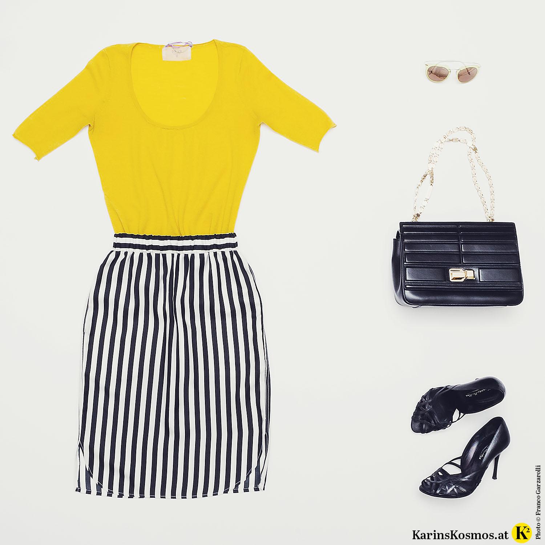Produktfoto mit gelbem Kaschmir-Shirt, Seidenrock mit schwarz/weißen Streifen, Sonnenbrille, Ledertasche mit goldenem Henkel und schwarzen Pumps.