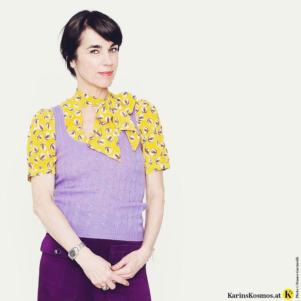 Frau trägt eine gelbe Seidenbluse zu fliederfarbenem Pullunder und violetter Short.