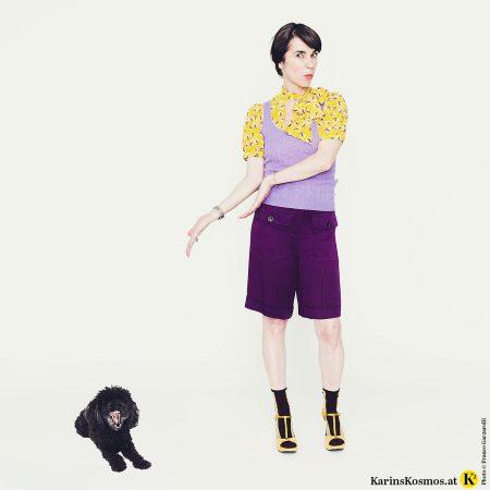 Frau mit gelb-gemusterter Bluse, lila Pullunder, violetter Short und gelben Sandalen. Daneben Toypudel der gähnt und Farben nicht so sieht.