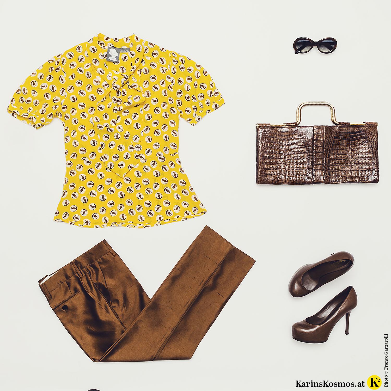 Produktfoto mit gelber Seidenbluse, brauner Seidenhose und Sonnenbrille, Abendtasche und Pumps in Braun.