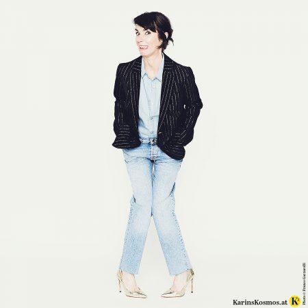 Frau in den Wechseljahren in Jeanshemd und Jeans mit dunklem Blazer.