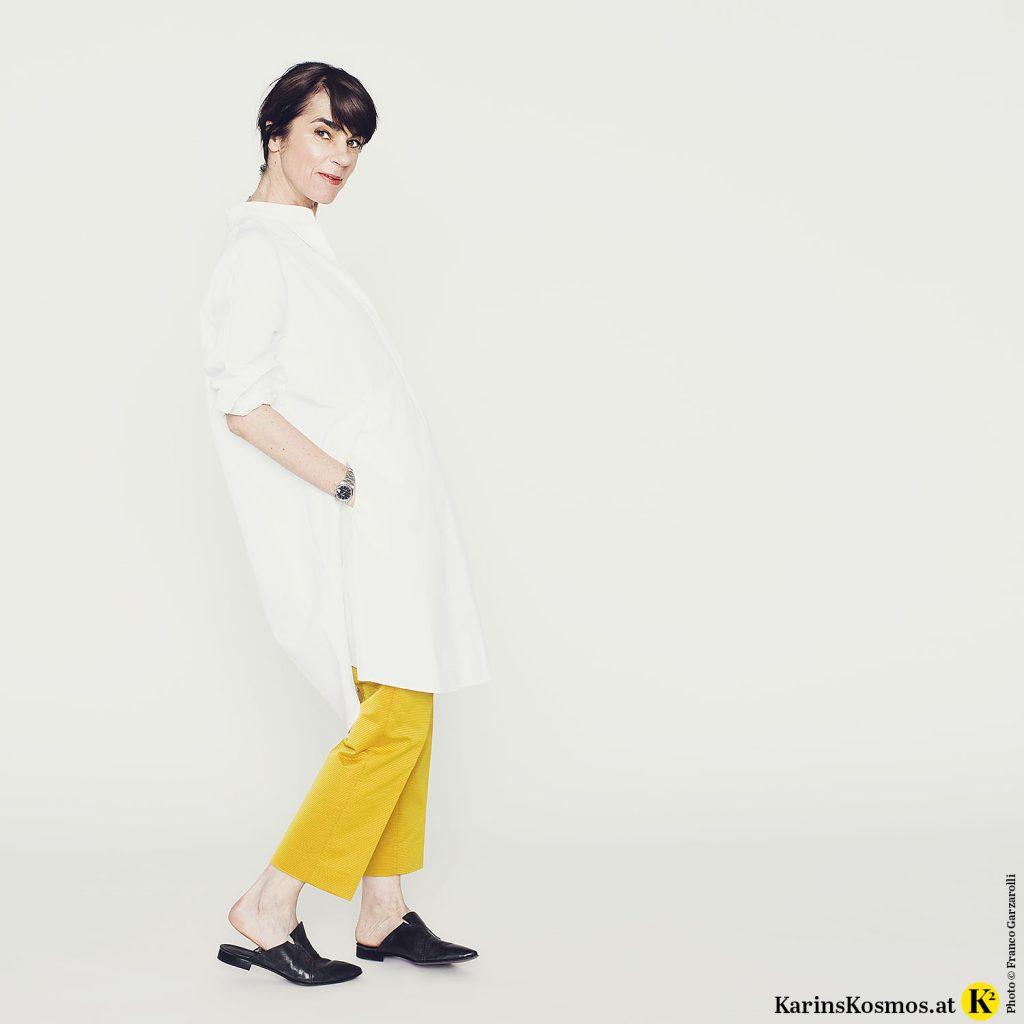 Frau in weißem Hemdkleid mit gelber Seidenhose und schwarzen Mules.