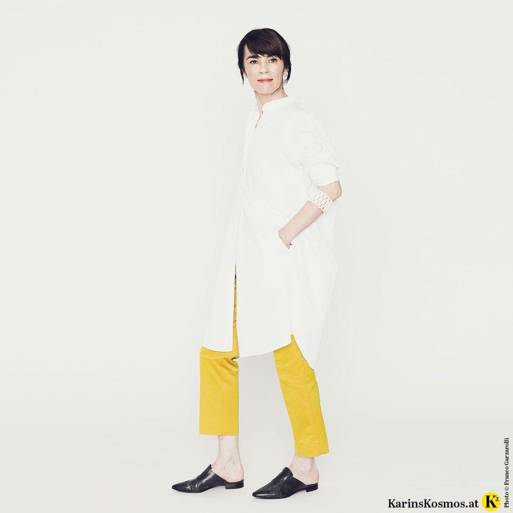 Frau mit weißem Hemdkleid, gelber Seidenhose und schwarzen Pantoletten.