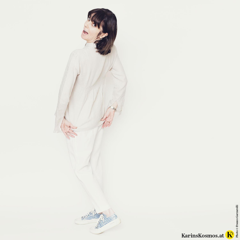 Frau in Sommeroutfit bestehend aus beiger Leinenbluse und weißer Hose.
