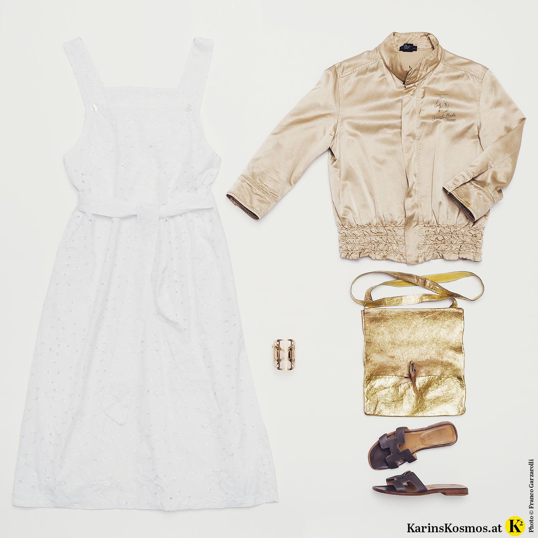 Produktfoto mit weißem Kleid, beiger Bomberjacke, goldenem Armreif und Tasche und braunen Leder-Slippers.
