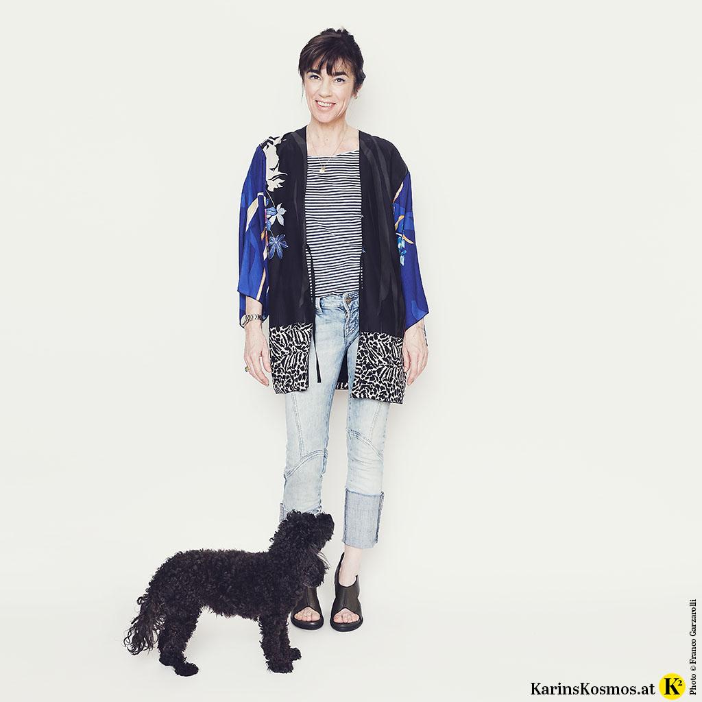 Foto mit Frau in Kimono zu Jeans und T-Shirt, davor steht ein schwarzer Toypudel.
