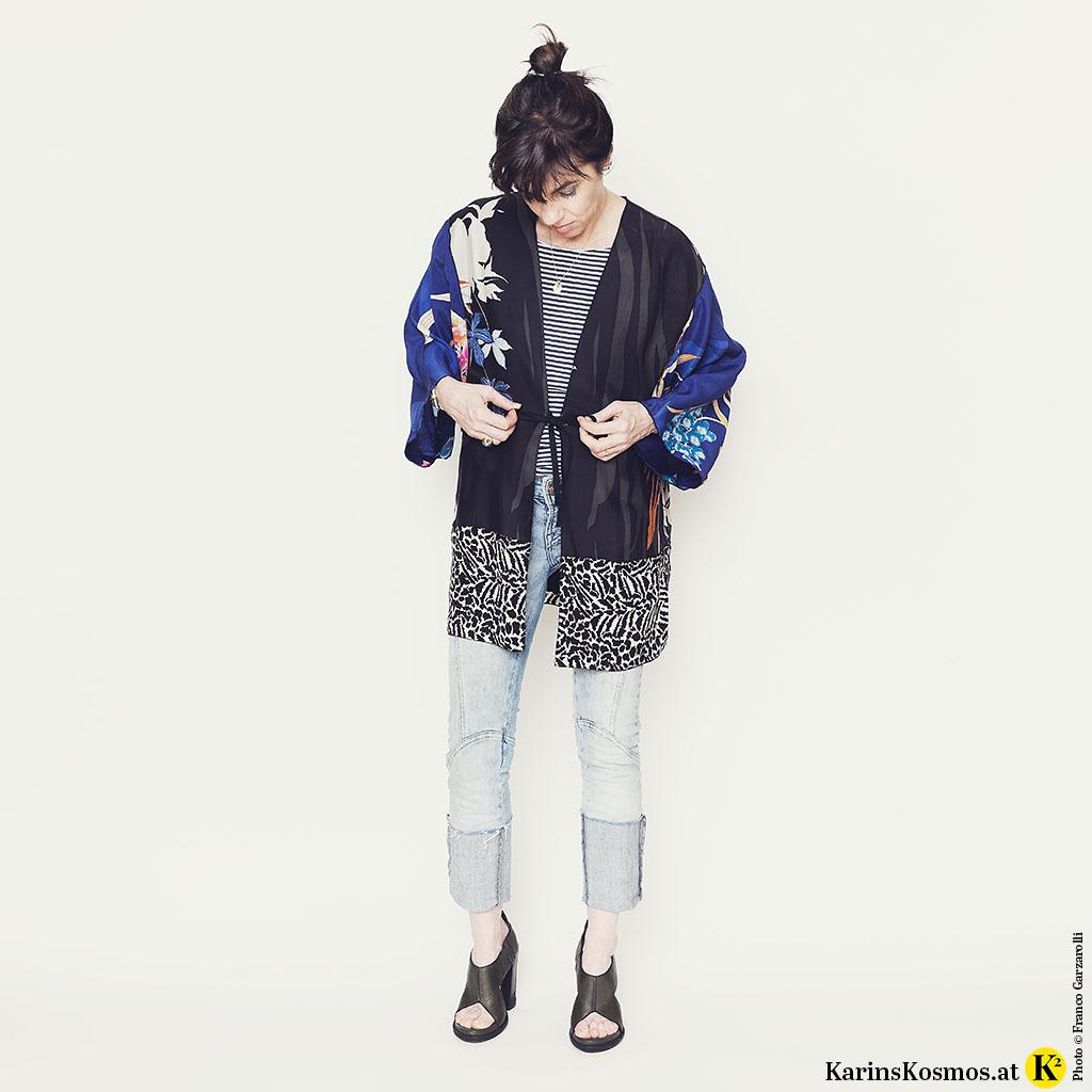 Frau in buntem Kimono mit Jeans, Streifen-Shirt und Sandalen.
