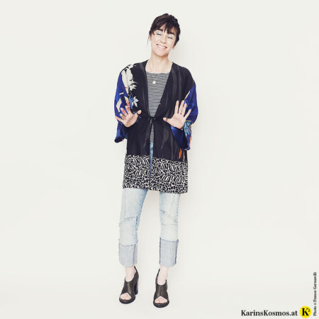 Frau mit einem Kimono, Streifen-Shirt, Jeans und Sandalen.