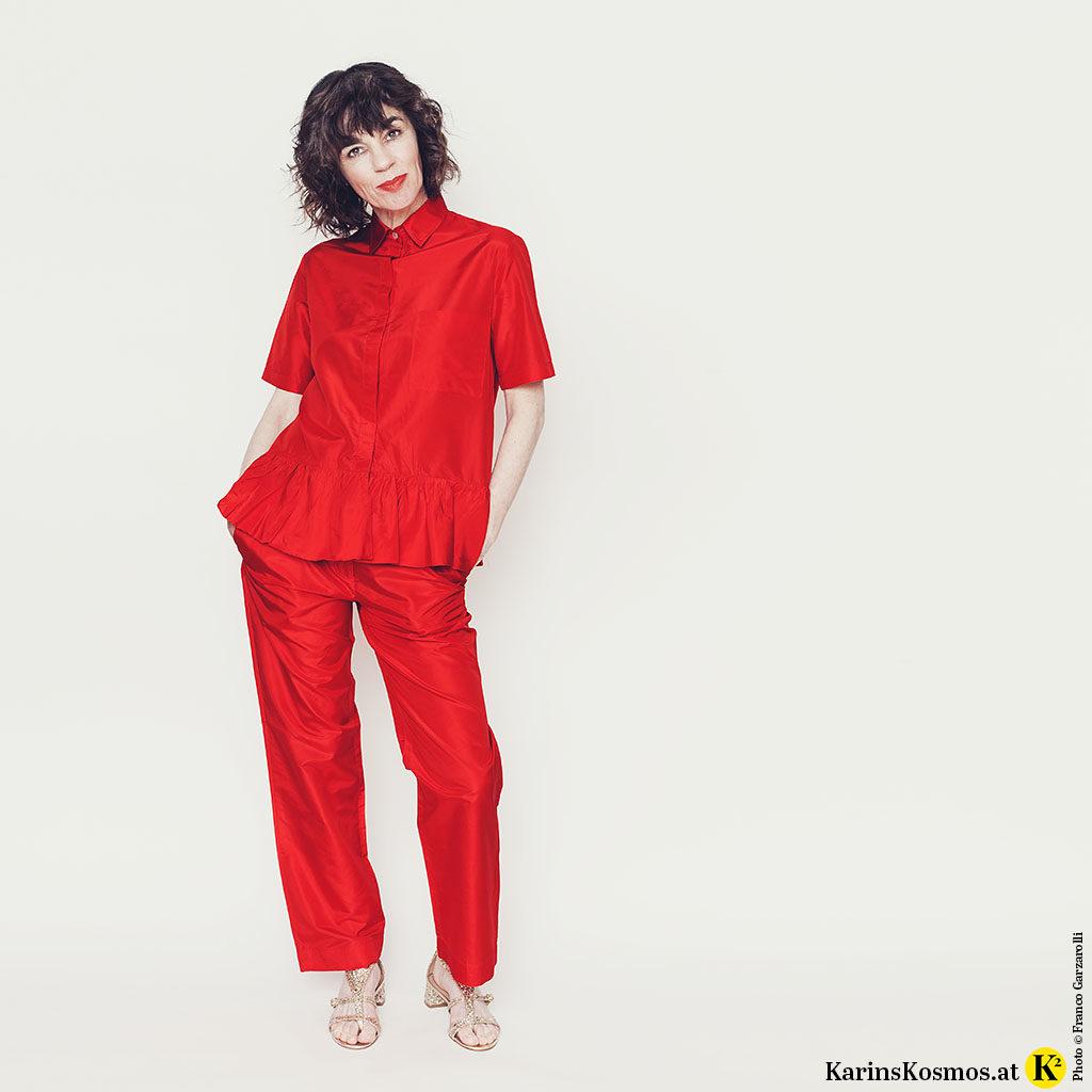 Frau in einem Seidenanzug in Rot.