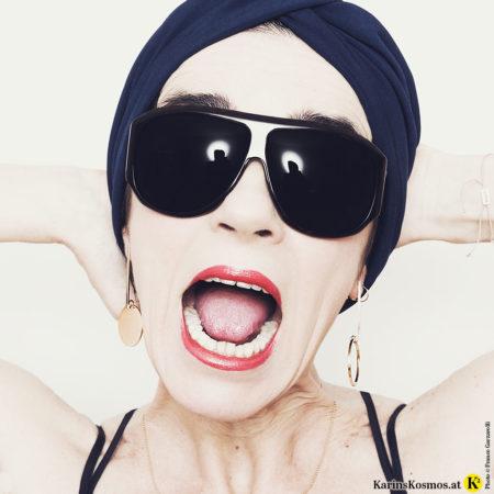Portrait einer Frau mit Sonnenbrille und Turban im Haar.