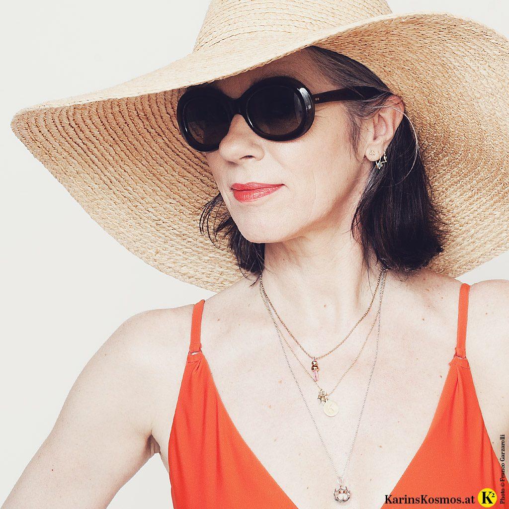 Frua im Badeanzug mit Sonnenbrille und Sonnenht zum Thema Sonnenschutz.
