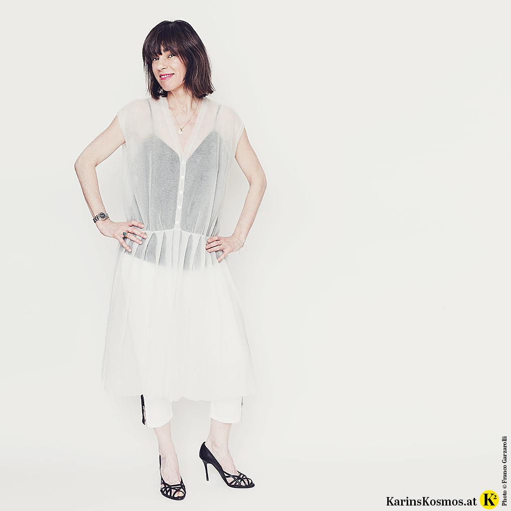 Frau in einem transparenten Kleid aus Metallic-Strick mit Top und Hose darunter.