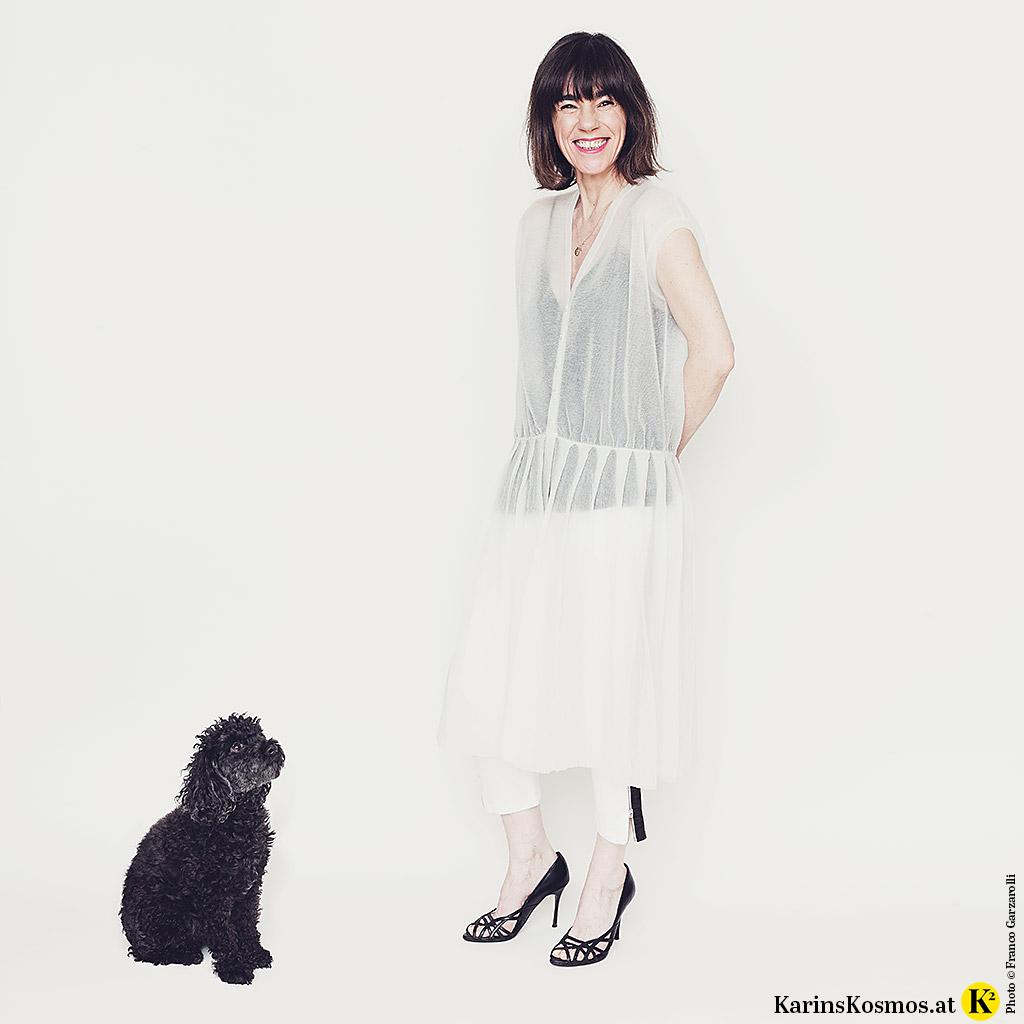 Frau in Kleid aus Metallic-Strick, daneben ein schwarzer Toy-Pudel.