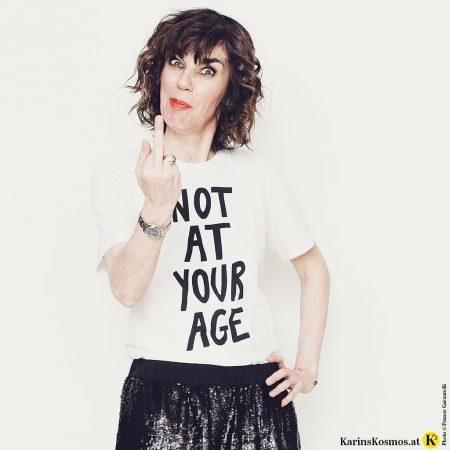 Frau mit Logo-Shirt und dazu Hose mit Pailletten.