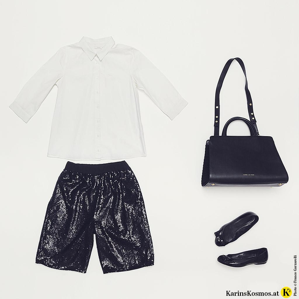 Produktfoto mit weißer Bluse, schwarzer Pailletten-Shorts, Business-Bag und Lack-Ballerinas.