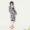 Frau in Seidenkleid und Slipdress, dazu eine Metallic-Clutch und rote Satin-Sandalen.