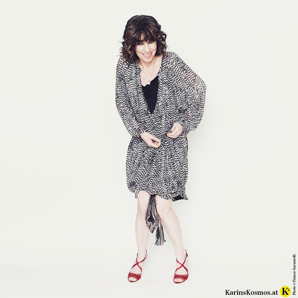 Frau in einem Seidenkleid mit Slipdress darunter. Dazu trägt sie rote Sandalen.