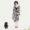 Frau in Seidenkleid mit Satin-Sandalen und daneben sitzt ein Toypudel.