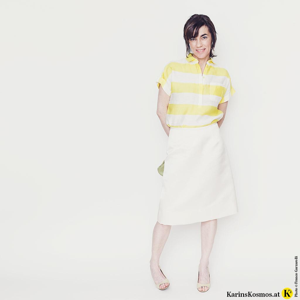 Frau in einem Satinrock in Weiß, dazu gelb-weiß-gestreifte Bluse, Peeptoes und Clutch in Lindgrün.