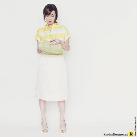 Frau mit Satinrock in weiß, dazu Leinenbluse, Heels und Clutch.