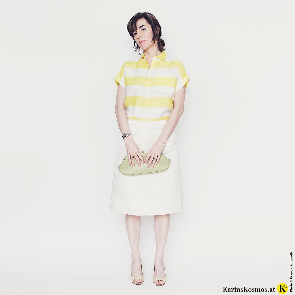 Frau in weißem Satinrock mit Leinenbluse, Heels und Clutch.