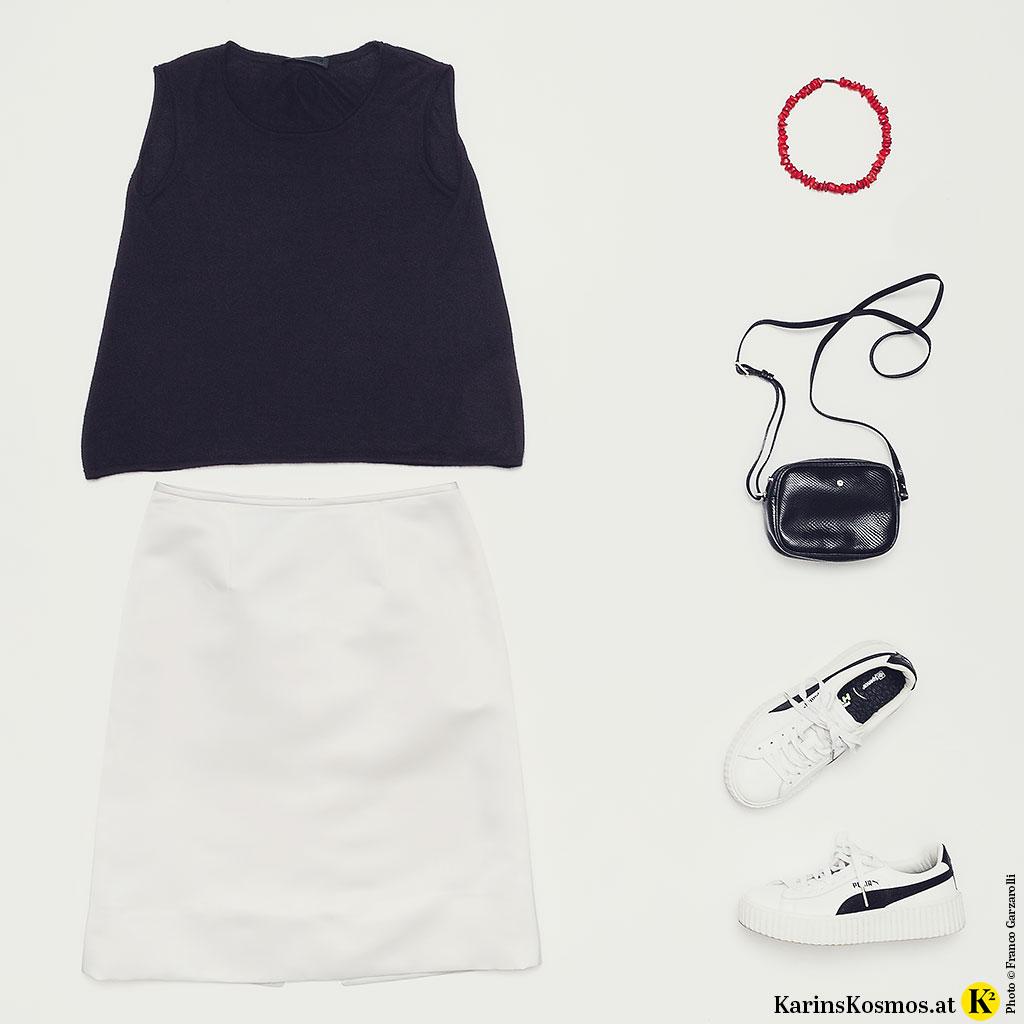 Produktfoto mit schwarzem Kaschmir-Top, Satinrock in Weiß, Sneakers, Umhängetasche und Korallen-Collier.