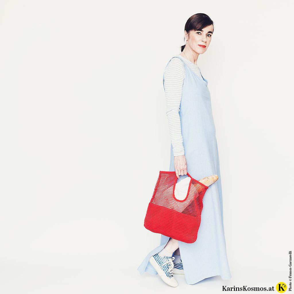 Frau in einem Leinenkleid für den Sommer mit Shirt darunter, Sneakers und einer Einkaufstasche.