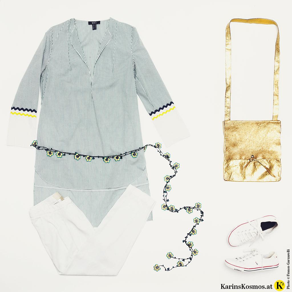 Produktfoto mit Tunika für den Sommer, weißer Hose, buntem Gürtel, goldener Tasche und weißen Sneakers.
