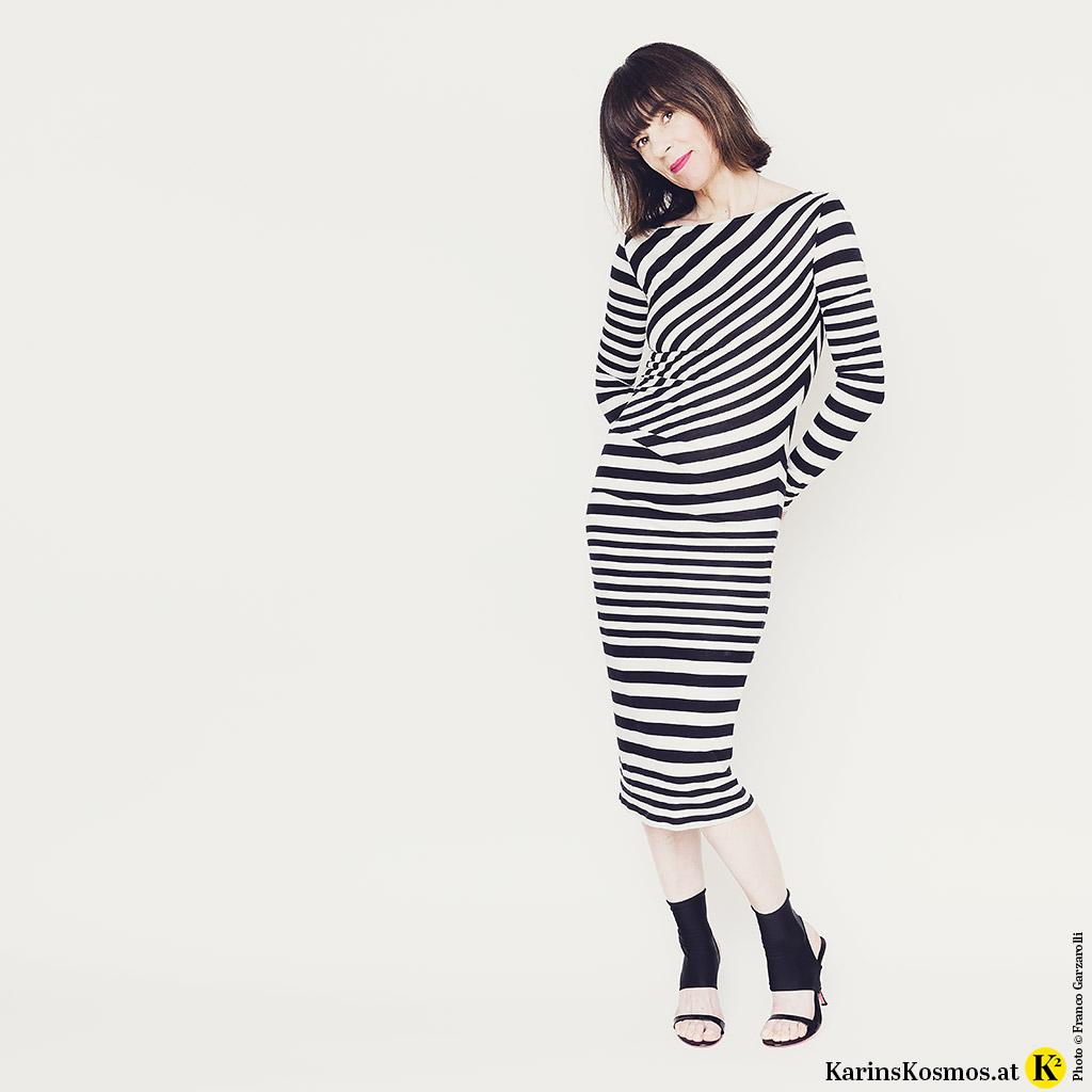Frau in einem Kleid mit schwarz/weißen Streifen und Sandalen.